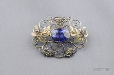 Arts & Crafts Purple Sapphire Brooch, bezel-set with a cushion-cut sapphire measuring approx. 13.30 x 10.60 x 8.22 mm, within a gold and silver scrolling grapevine frame, lg. 1 3/4 in.
