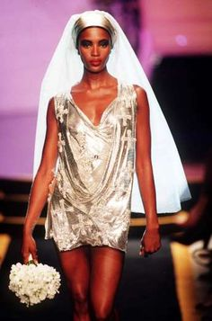 Naomi Campbell embodied a Versace bride on the runway in July 1997. The supermodel walked in the designer's Autumn/Winter Collection in Paris that summer wearing this slinky cross-emblazoned silver minidress with a veil and a bouquet.