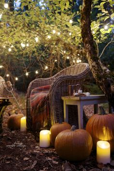 Wicker chairs, pumpkins, plaid throws, twinkling lights make the perfect setting for an chilly night.