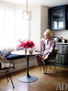 Poppy Delevingne, wearing silk pajamas by Olivia Von Halle, in the kitchen of her west London home. (fashion styling by Aurelia Donaldson.) Pendant fixture by Kaia lighting; Saarinen table for Knoll; Rattan chairs by Cox & Cox. Saarinen Tisch, Saarinen Table, Dining Nook, Dining Room Table, Kitchen Nook Bench, Nook Table, Corner Table, Kitchen Corner, Dining Chairs