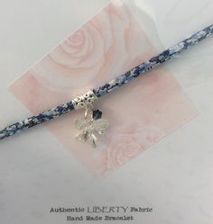 Narrow Liberty ribbon bracelet with orchid charm on bail.