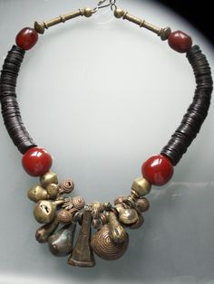by Anne Marie ~ BeadArt Austria | A lovely collection of all together about 23 antique bronze bells from the Yoruba Tribe in Nigeria , in various shapes and sizes are the focal point of this necklace. Make quite a sound ! Large bronze beads and African cherry amber resin beads are on each side.     The neckpart is made with old coconut heishi disks, more red resin beads and old brass tubes.
