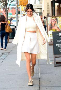Kendall Jenner usando halter top e em um look monocromático todo branco, com saia e sobretudo, ultra elegante!