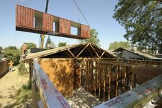 Shane Baesemann, of Baesemann Design Build, and his team lift the first of the containers into place at the back of Nick and Becky Brown's house in the 500 block of N. Highland Street in Tulare.