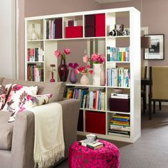 This white open bookcase divides one large space into two separate functions~ living and dining…