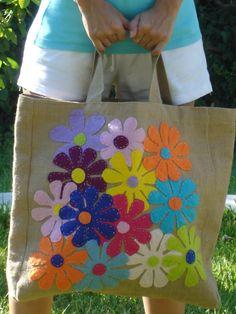 Knip de bloemen uit en bevestig ze met naald en draad of met een dun laagje textiellijm op een katoenen of jute tas.