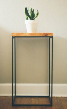 Ikea hack side table using a metal frame clothing hamper topped with a piece of stained wood