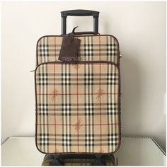 BURBERRY HAYMARKET ROLLING CARRY-ON LUGGAGE BURBERRY HAYMARKET ROLLING CARRY-ON LUGGAGE | ❗️AUTHENTIC | One flat carry handle on the top of the bag • one carry handle on the side of the bag • Extendable handle for wheeling the suitcase • Two wheels, two feet on the self fabric base • 1 exterior zip pocket in front • 1 interior zip pocket • wrap around zip closure | what you see is what you get. please keep in mind that there is minor damage to this because it has been through travel • does…