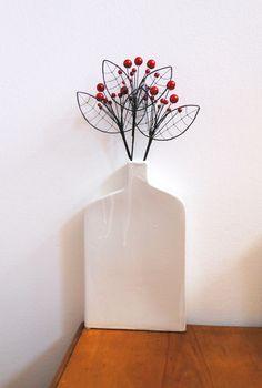 červený květ -zápich Zápich je vyroben ze žíhaného drátu, který je dozdoben perleťovými korálky. Dálka je cca 35cm a průměr je cca 9,5cm. Zápich hezký vypadá v květináči nebo v suché vazbě. Drát je ošetřen proti korozi, ale ve vlhkém prostředí může chytit patinu. Cena za kus.