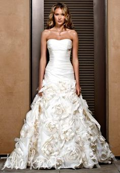 Ball gown wedding dress with a sweetheart with a dropped waist. the ruching almost looks like roses.