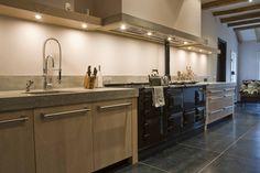 Maatwerk massief eikenhouten keuken met 2 Aga fornuizen en betonnen aanrechtbladen. De bladen zijn in het werk gegoten. Kooflijst afzuigkap ook van beton. Viking handgrepen.
