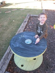 Upcycled wooden cable spool with chalk holder. So amazing - keep the chalk mess outside! I love this idea.