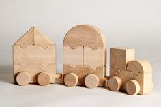 Wooden Folding Train - Arboline  The wooden toy consists of 11 wood blocks designed as a geometric shape which allows them to be put together in different combinations creating a running train.