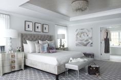 Glamorous contemporary gray and silver bedroom features two Bernhardt Audrey Three-Drawer Nightstands positioned in front of windows covered in sheer white curtains lit with Global Views Cloud Lamps flanking a gray velvet tufted wingback bed dressed in white bedding topped with layered gray and purple pillows.