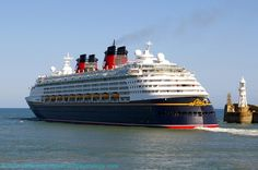 MS Disney Magic Cruise Ship Departure, Western Entrance, Dover Harbour, Kent, England, UK. Vessel owned by Disney Cruise Line. Arrived from Lisbon (Portugal) en route to Oslo (Norway). Ship data: Call Sign C6PT7, IMO 9126807, MMSI 308516000; Registered Nassau (Bahamas). View: Prince of Wales Pier with English Channel (left) and Admiralty Pier (right). Lighthouse is Admiralty Pier Light. Port of Dover travel, tourism, and holiday photo. More information at…