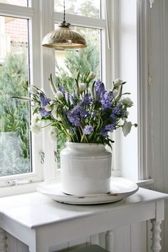 Quaint blue and white flower arrangement in a Scandinavian setting.