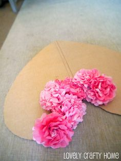 Coffee filter flowers arranged on a cardboard base for a Valentine's heart display