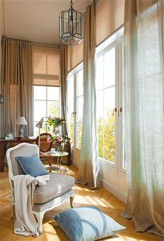 Butaca frente a gran ventanal con cortinas de colores degradados agua y tostados