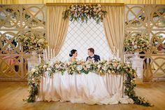 GORGEOUS wedding reception table for the bride & groom! Love all the lush floral accents! Lots more beautiful photos of the wedding on this website.