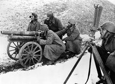 Guerra greco-italiana, noviembre de 1940: tropas griegas en las montañas de Albania dispuestas a abrir fuego contra la infantería italiana con un cañón de 65 mm. Nótese el observador de artillería con el telémetro, calculando la trayectoria de los proyectiles.