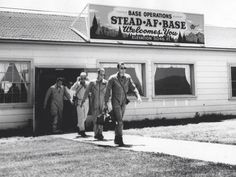 Original seven Mercury astronauts undergoing survival training at Stead AFB, exit the base operations building.