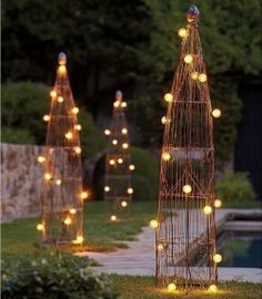 Fun, structural, lighting feature for the garden.  Can I make these with large tomato cages wrapped with grapevine and patio lights or twinkle lights?  This group of 3 is nice. a-secret-garden
