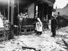 "Undaunted by a night of German air raids in which his store front was blasted, a shopkeeper opens up the morning after for ""business as usual"" in London."