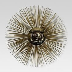 The sharp lines and round shapes of the Gold Starburst Decorative Wall Sculpture from Project 62™ make it suitable as a wall accent piece in any room. Consider it as a metallic pop in a gallery wall full of paintings and portraits, or place it alone over a doorway or table, as it can easily stand on its own. The many overlapping rods give it depth, and the center orb gives it texture, but this sculpture won't overwhelm your decor. <br><br>1962 was a big year. Modernis...