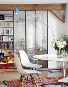 I like how the bookshelf, glass sliding door, the blue lamp and the white furniture all come together to form layers that really gel and still made the eye travel through all that depth.