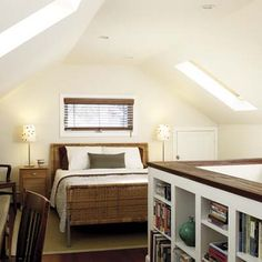 A half-wall lined with bookshelves encloses the staircase of this attic bedroom. | Photo: David Prince | thisoldhouse.com