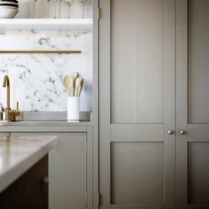 white marble backsplash, brass accents in the kitchen, greige kitchen cabinetry.Sophia Shibles Interior Design is inspired by this . Beige Kitchen Cabinets, Brass Kitchen, Kitchen Backsplash, Kitchen And Bath, New Kitchen, Swedish Kitchen, Kitchen Grey, Kitchen Countertops, Shaker Cabinets