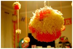 Birthday party decorations - various sized pom poms with googly eyes hanging from the ceiling