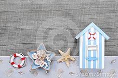Beach hut and seashells on a grey wooden background for travel