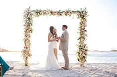 modern elegant floral arch for ceremony backdrop covered in loads of blush pink and white flowers | Beachside Ceremony with the Dreamiest Floral Arch EVER