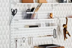 An Elfa storage board in a home office, with attached hooks and metal shelves for storing office supplies.