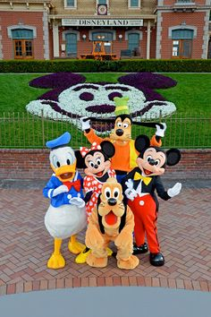 Disneyland Minnie, Mickey, Donald, Pluto, and Goofy in front of the train station
