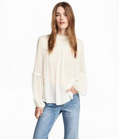 White. Wide, straight-cut blouse in plumeti chiffon. Small stand-up collar, opening at back of neck with button, and gathered yoke with narrow ruffle trim.