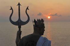A U.S. Sailor dressed as Poseidon, the Greed god of the sea, aboard aircraft carrier USS Carl Vinson (CVN 70) participates in a Crossing the Line Ceremony, an ancient seafaring tradition to mark the ship's passing of the Equator while under way in the Pacific Ocean May 12, 2011