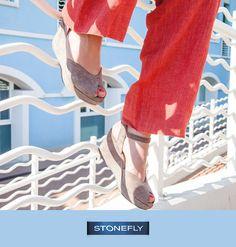 Più estate di così! La luce tersa del lungomare fa risaltare i colori di questo splendido gioco di contrasti tra il bianco e l'azzurro dell'ambiente, su cui spiccano il corallo dei pantaloni in lino ed il color sabbia delle zeppe Marlene, il cui elegante taglio peep-toe fa intravedere lo smalto, naturalmente in tinta!