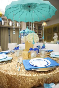 Umbrella centerpieces for baby shower. Blue white and gold baby shower color palette. La Tavola Linen New York Gold.| Lovelyfest Event Design | Royal Blue Baby Shower #babyshowercenterpieces #baby #shower #centerpieces #umbrella