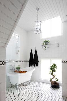 Yli kolme metriä korkeaan kylpyhuoneeseen tulee runsaasti valoa kahdesta päällekkäisestä ikkunasta. Suihkuseinä ja kattovalaisin on hankittu Bauhausista ja tassuamme K-raudasta.