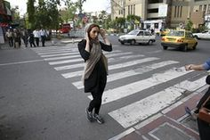 Daily Struggles of Iranian people, especially women : An Iranian woman adjusts her head scarf while crossing a street in downtown Tehran, Iran.