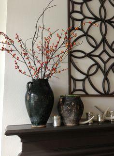 This mantel is decorated with rustic vases. | Interior designer: Carla Aston