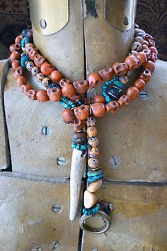 Necklace   Helen Nelson-Reed. 'Tibetan Inspired Lariat'.  The skull beads are stone, enhanced to a midrange, soft coral shade.  They've been antiqued but are contemporary. Other beads include turquoise heishi, the brass ring on one end is antique, from Africa, tribal beads, antler and brass complete the design.