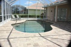Completed pool renovation.  Concrete brick coping and pavers with Pebble Tec Sedona Red interior finish.