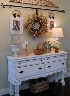 Use a curtain rod to hang a wreath or quilts! What a fantastic way to be able to swap things out seasonally! I want one of these over my couch!----  I use to have a curtain rod over my couch to hold a quilt...it also hid a door we rarely used, but you could still get to the door when you pushed the quilt away!