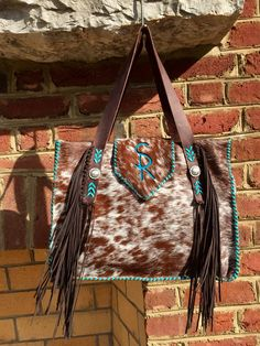 The Buckaroo Tote, with the owner's initials in turquoise suede on the flap, hand cut suede fringe and turquoise leather lace stitching. Custom purses and totes from gowestdesigns.us