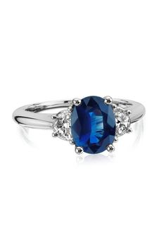 Simply stunning, this classic sapphire and diamond ring features a deep blue, oval sapphire and two half-moon diamond sidestones. This platinum three-stone ring is a unique diamond engagement ring option.