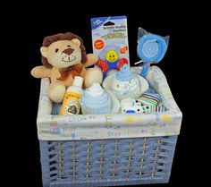 Baby Gift Basket ~ 1 blue basket with liner, 1 handmade blanket - reversible,1 plush lion, 2 onesies, 4 washcloths, 1 baby spoon, 1 baby lotion,1 toy/teether, 1 pacifier, 1 pair of socks. via Etsy