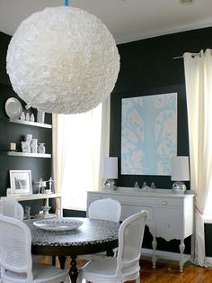 This massive light fixture is a paper lantern covered in coffee filters.  It looks like a giant ball of carnations, in a cool way!